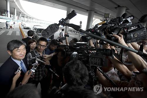 """韩国外交部朝鲜半岛和平交涉本部长、六方会谈韩方团长赵太庸(左)21日抵达北京,一抵达机场就遭到记者的""""围攻""""。(韩联社)"""