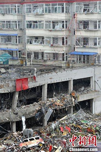 6月21日,山西朔州饭店爆炸现场,事发饭店背后的楼房受损严重,民众纷纷搬离。韦亮 摄