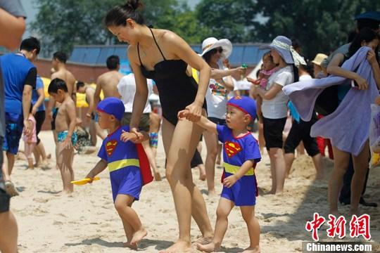6月23日,一对身着超人图案泳衣的双胞胎小朋友在妈妈的带领下来到北京朝阳公园奥运沙滩上游玩。中新社发 苏丹 摄