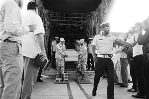 装有遇难中国公民遗体的棺木被抬下飞机 新华社发