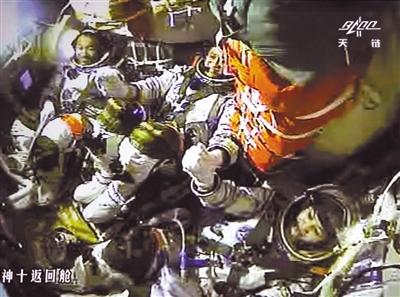 昨日,天宫一号与神十飞船成功实现手控交会对接。3位航天员手拉手庆祝成功(摄自北京航天飞控中心大屏幕)。新华社发(张晓祺 摄)
