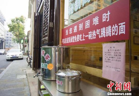 """图为:面店门前张贴着:""""当您遇到困难时,可以在成良面馆免费吃上一碗热气腾腾的面""""。 李晨韵 摄"""