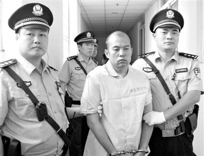 """6月25日,在河北省邯郸市中级人民法院,司法警察押解王书金出庭。由于此案曾牵扯出19年前聂树斌案""""一案两凶""""的疑云,因此备受舆论关注。 新华社发"""