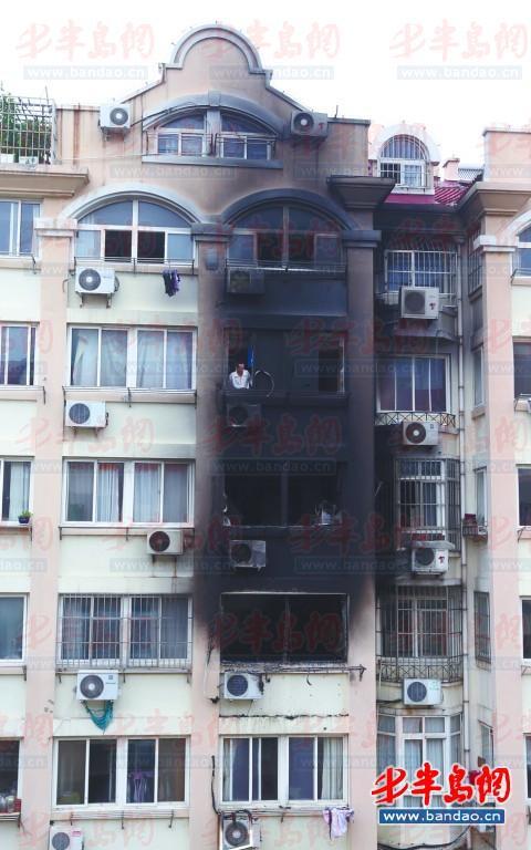着火居民楼被熏得漆黑,窗户都被烧坏了。