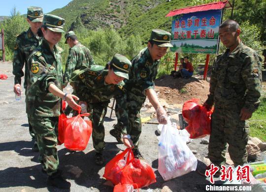 图为内蒙古呼和浩特边防指挥学校官兵在捡完垃圾后将垃圾统一带到山脚的垃圾回收点。白琥 摄