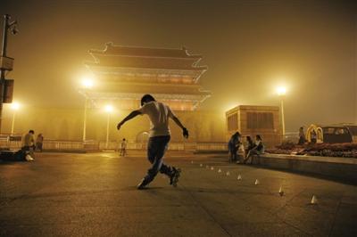 昨日,北京前门,轮滑少年在雾霾中练习。据市环保监测中心数据,昨日大部分地区空气受严重污染。新京报记者 王叔坤 摄