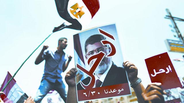 在开罗解放广场示威者手举穆尔西离开的标语游行。
