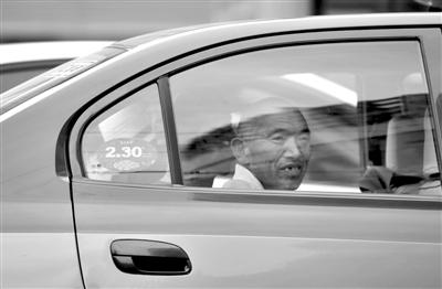 """市民坐在调价后的出租车上。从今天起,将不再有""""2元/公里""""的出租车。资料图片/新京报记者浦峰摄"""