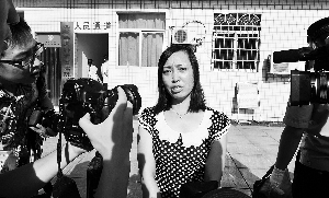 唐慧(右)在步入湖南省高级人民法院时被媒体包围。 新华社发