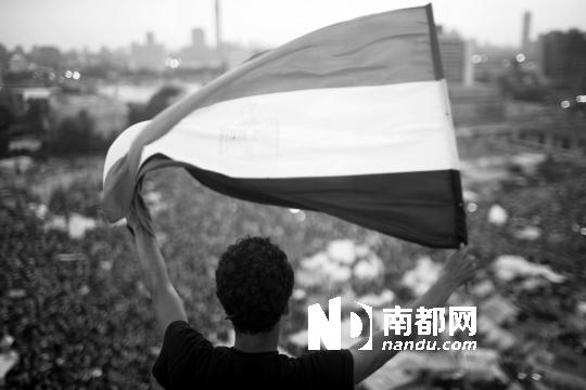 1日,在埃及开罗胜利广场,一名示威者高举旗帜反对总统穆尔西。