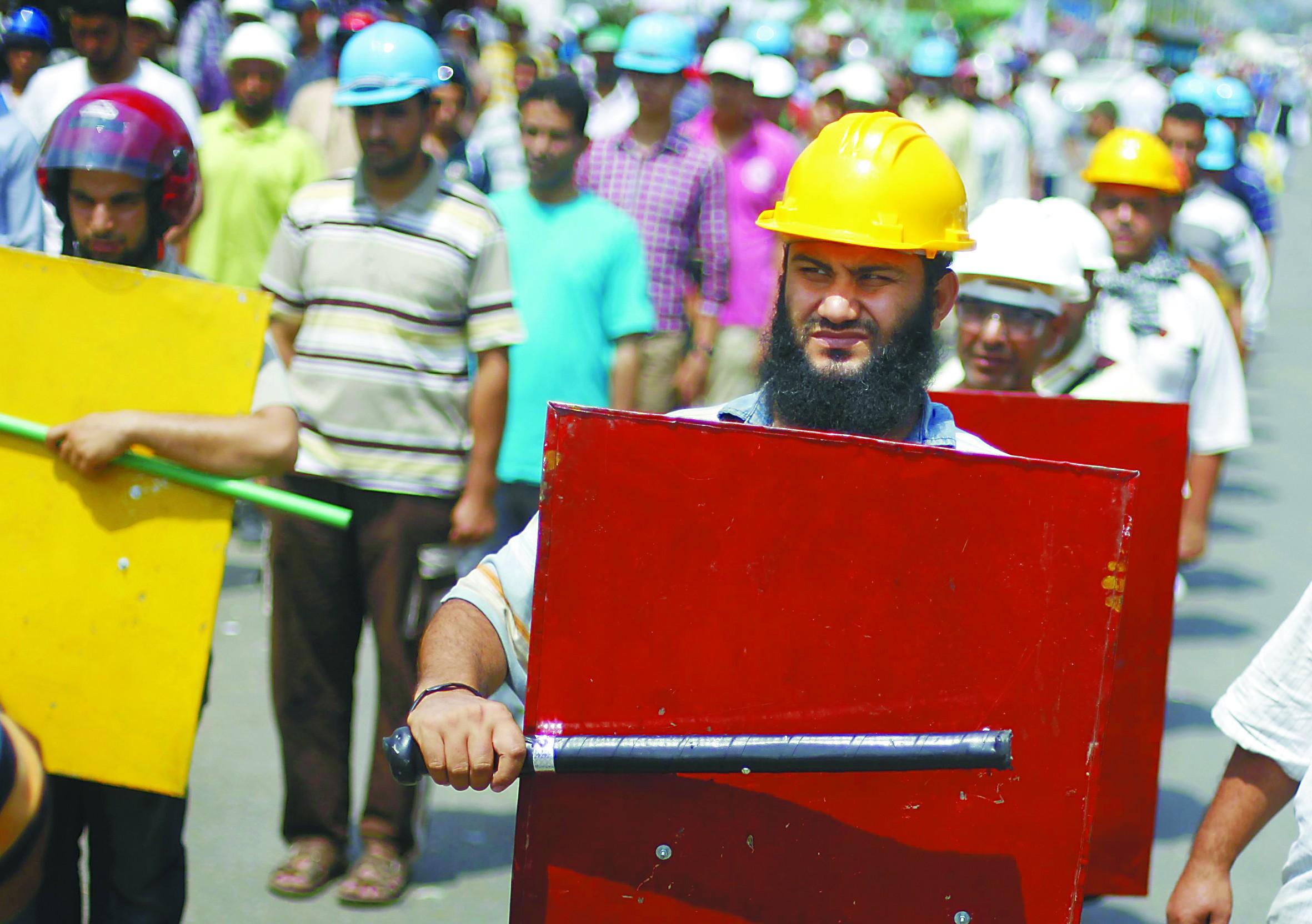 7月2日,埃及总统穆尔西的支持者手持棍棒、头戴安全帽在总统府附近举行游行。