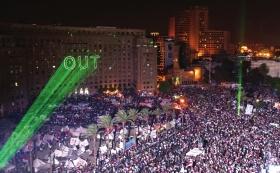 """7月2日,在埃及开罗解放广场,绿色激光投影在一座建筑上打出""""离开""""标语。图/新华社"""