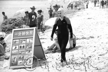 3日,在青岛第一海水浴场,一位游客全副武装。