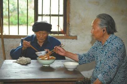 7月4日,家住成都双流太平镇前进村的老人付素清(左)和女儿吃饭,她一日三餐顿顿不离肉。