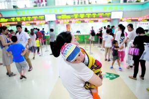昨日,上海市儿童医院,一岁半的睿睿已持续高烧两天,无精打采地趴在奶奶的肩膀上。申城连日高温,门急诊量剧增。 早报记者 孙湛 图