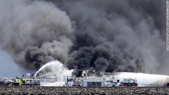 在飞机坠向地面后燃起大火,附近浓烟滚滚。