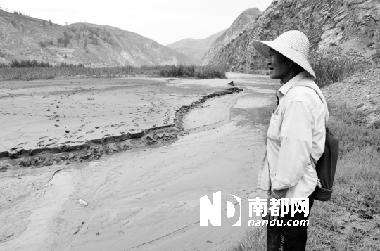 """村民张万珍看着已板结的土地说,最大的心愿是""""土地能变回以前那样""""。 南都记者 龙玉琴 摄"""