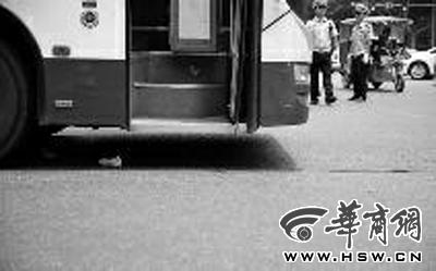 公交车车轮下还留有老人的一双鞋  邓小卫 摄
