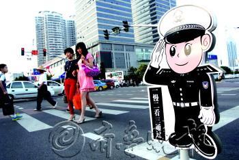 """7月11日,日照市区泰安路与烟台路路口,一卡通警察向路过的人们""""敬礼"""".图片"""