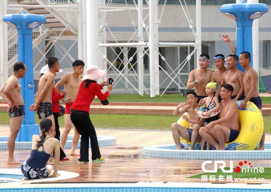 平壤/2013年7月11日消息,朝中社发布的图片显示了民众在平壤游乐...
