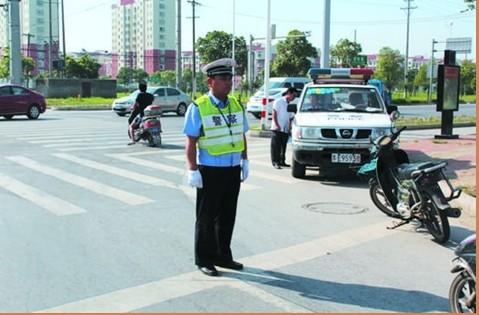 烈日下交警中队长坚守路口立马路 汗湿衣衫