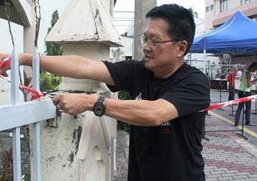 赖君万亲自拉起红白警戒线,协助鸡场街小贩封街。马来西亚《东方日报》