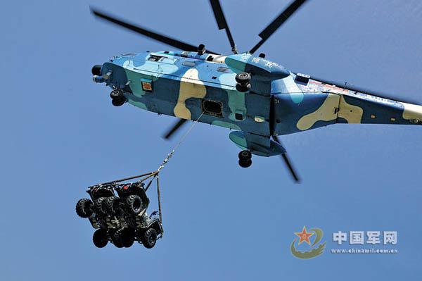 原文配图:空降兵某直升机团进行空投全地形车和指挥方舱吊挂试验性训练。