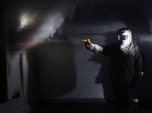 """7月19日,一位消防人员在测试""""火场快速降温弹""""灭火后火场的温度。新华社记者李文摄"""