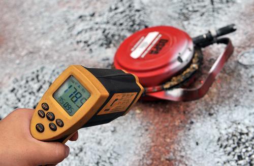 """7月19日,一位消防人员在测试使用后的""""火场快速降温弹""""的温度。新华社记者李文摄"""