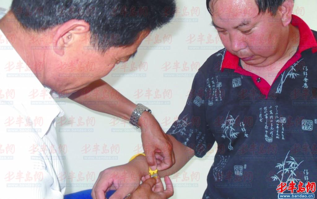 曹德华/作人员为残疾人佩戴黄手环。