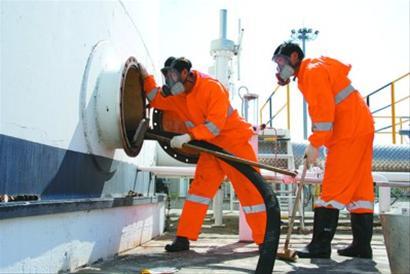 油库员通过直径不足1米的出入口进入油罐 计刚峰摄