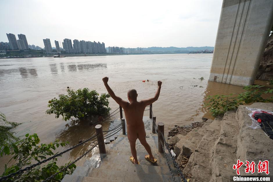 7月22日,重庆九龙坡区建设码头,探访重庆裸泳滩。图为通往河滩的道路被洪水淹没了大部分,裸泳爱好者们席地而坐,谈家常。中新社发渝友摄图片来源:CNSPHOTO
