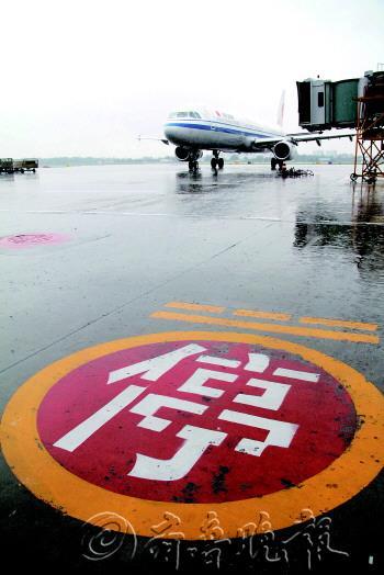 7月23日,青岛流亭国际机场,大雨导致多个航班延误,一架客机停在机场停机坪上等待复飞。 东方IC供图