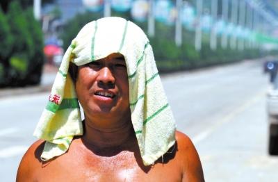 河北保定一市民用湿毛巾降温。
