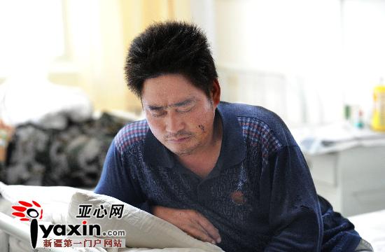 浑身疼痛的郑龙洋一想到妻儿的病情就立坐难安,一直不愿躺在病床上静养。亚心网记者 张万德 摄