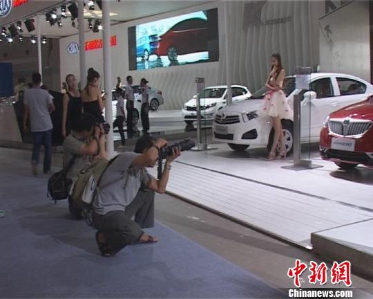 参观者正在为车模照相。 张怡 摄