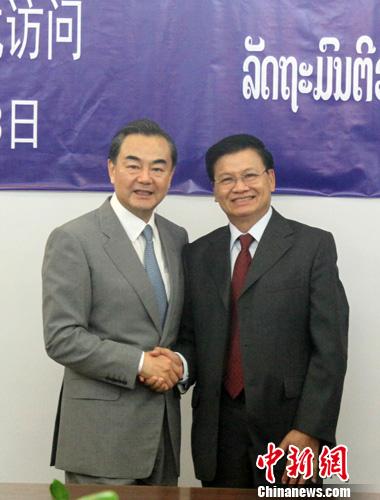 8月3日,中国外交部长王毅在老挝首都万象与老挝副总理兼外交部长通伦举行会谈。图为王毅(左)与通伦在会谈开始前握手。中新社发 张明 摄