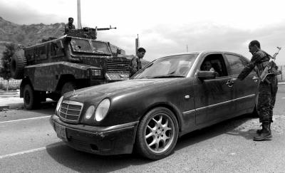 8月4日,在也门首都萨那一条通往美国大使馆的道路上,士兵检查来往车辆。新华社发