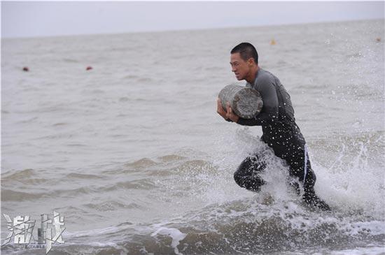 《激战》海边训练照:张家辉在海边抱石墩快跑