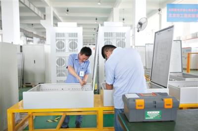 8月6日,京仪绿能研究人员正在组装智能汇流箱。新京报记者 侯少卿 摄