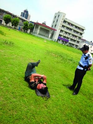 男子躺在草坪上,民警在劝他 通讯员 陈晓菲/摄