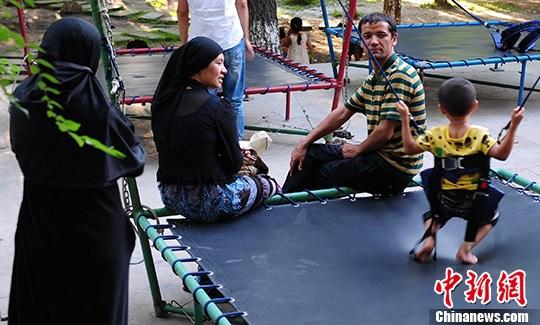 8月8日是新疆穆斯林群众的传统节日肉孜节。7日下午,几位穆斯林群众带着孩子,在乌鲁木齐市水磨公园玩跳床。中新社发 马新龙 摄