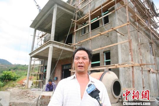 四川攀枝花盐边县纳尔河村民冯国清在正在修建的新房前接受记者采访。 高寒 摄