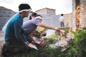 爆炸发生后第三天,在发生爆炸的项目部办公室墙外,王小平的大儿子王鹏和弟弟妹妹们点燃纸钱,祭奠父亲