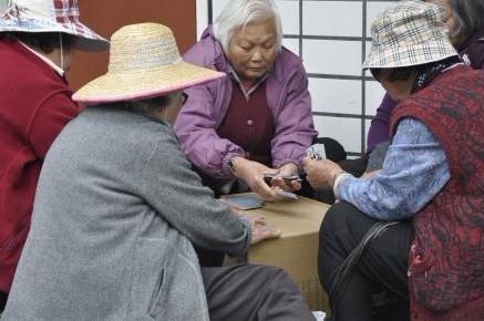 一群华人老太在广场上玩扑克。美国《侨报》
