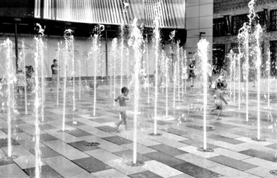 昨日傍晚,三里屯太古里广场,多名小朋友在喷泉中嬉戏。 新京报记者 李馨 摄