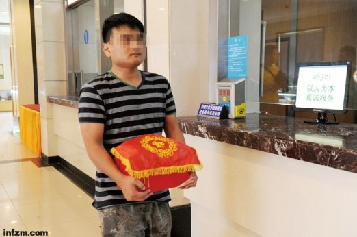 2013年7月15日,长沙明阳山殡仪馆,曾成杰之子曾贤领取到父亲骨灰。 (东方IC/图)