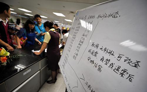 8月14日,旅客正在海口美兰机场办理机票改签手续。新华社记者 郭程 摄