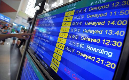 8月14日,旅客正在海口美兰机场查看航班信息。新华社记者 郭程 摄