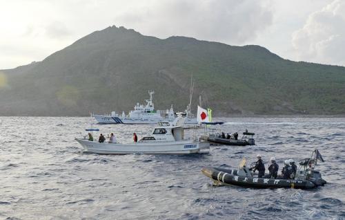 18日,日本右翼团体乘坐的渔船(中)进入钓鱼岛附近海域后被日海上保安厅船只包围并勒令离开。